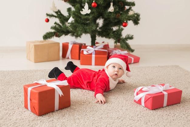 크리스마스 트리 옆에 바닥에 크롤링 산타 클로스 옷을 입고 귀여운 아기 소녀