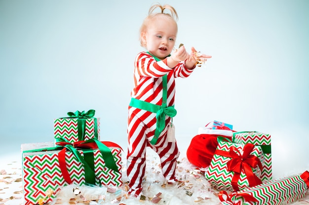 Cute baby girl wearing santa hat posing over christmas background. standing on floor with christmas ball. holiday season.