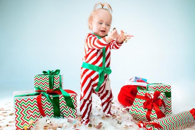 크리스마스 배경 위에 포즈 산타 모자를 쓰고 귀여운 아기 소녀. 크리스마스 공을 바닥에 서. 휴가 시즌.