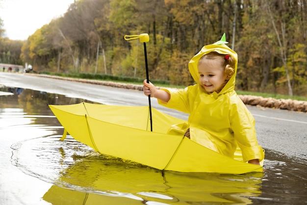 Милая девочка носить желтый стильный плащ розовые резиновые сапоги, сидя в зонтике в луже.