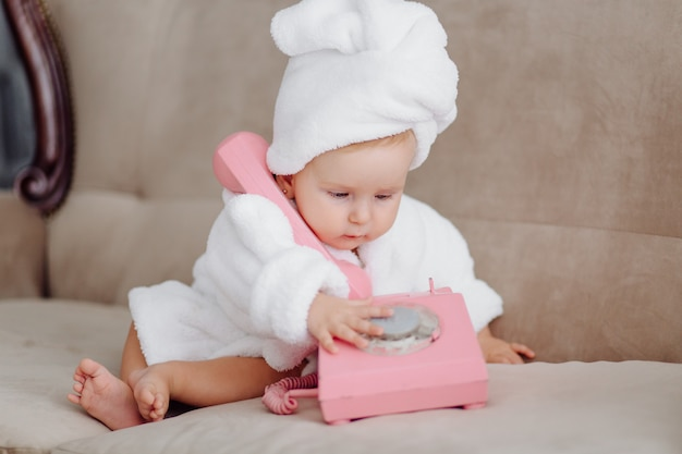 Cute baby girl in white bathrobe