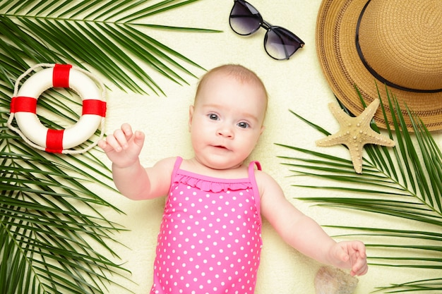 Cute baby girl with beach accessories. holidays at sea with baby, summer concept