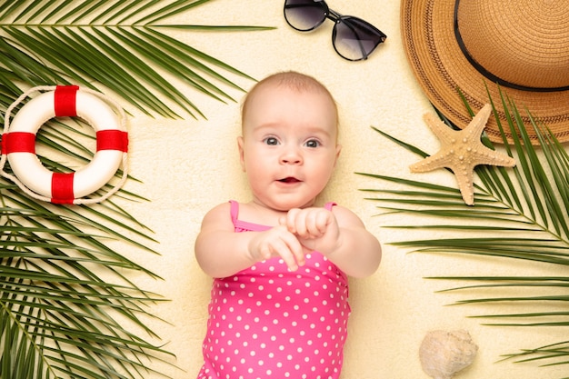 Cute baby girl with beach accessories on light background. holidays at sea with baby, summer concept