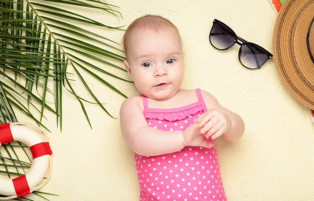 Cute baby girl with beach accessories on light. holidays at sea with baby, summer concept