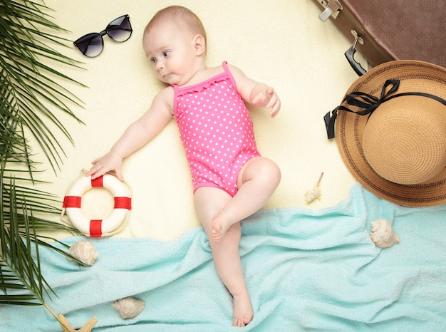Cute baby girl with beach accessories on light. holidays at sea with baby
