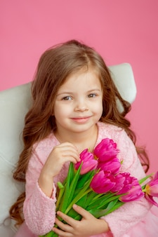 Cute baby girl with a bouquet of tulips in her hands on a pink background
