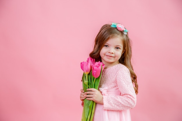 Cute baby girl with a bouquet of tulips in her hands