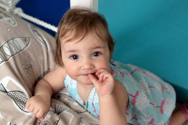 カメラを見てドレスを着て茶色の目を持つかわいい女の赤ちゃん。女の子は子供部屋で楽しんでいます