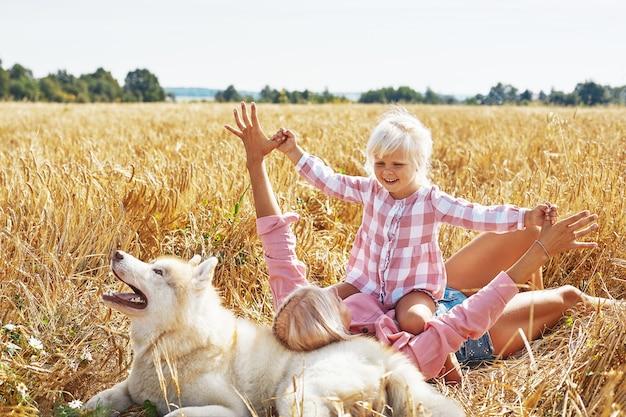 엄마와 밭에 강아지와 함께 귀여운 아기 소녀. 행복 한 젊은 가족은 자연에서 함께 시간을 즐길 수 있습니다. 엄마, 작은 아기 소녀와 강아지 허스키 야외 휴식. 공생, 사랑, 행복 개념.