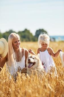 엄마와 밭에 강아지와 함께 귀여운 아기 소녀. 행복 한 젊은 가족은 자연에서 함께 시간을 즐길 수 있습니다.