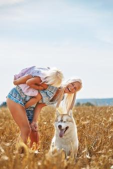 Милая девочка с мамой и собакой на пшеничном поле.