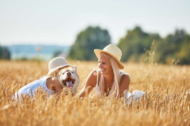 Cute baby girl with mom and dog on wheat field. happy young family enjoy time together at the nature.