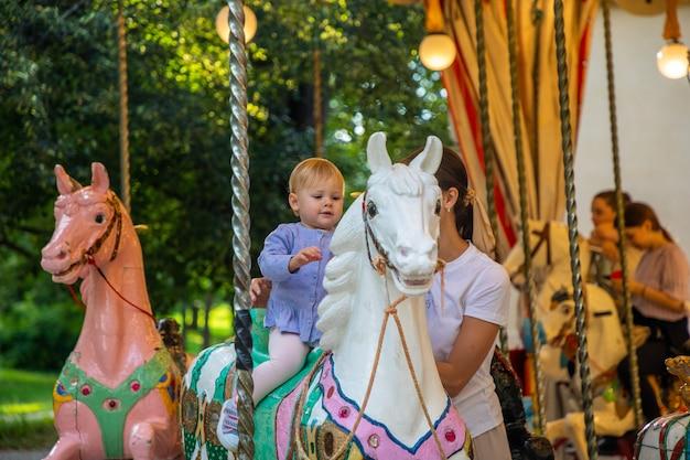 Милая девочка с матерью на лошади старой ретро-карусели прага чешская республика