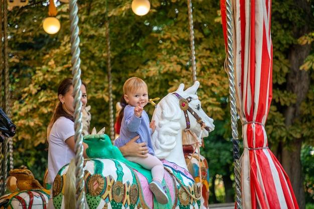 Милая девочка с матерью на лошади старой ретро-карусели прага чешская республика Premium Фотографии