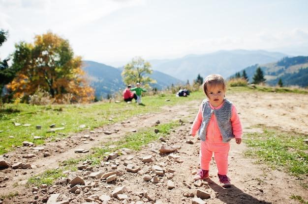 山で歩くかわいい赤ちゃんの女の子。小さな発見者。