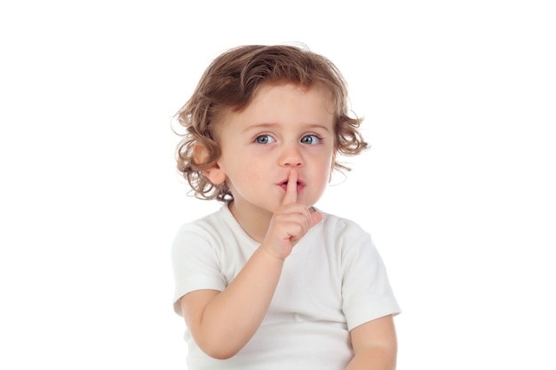 Cute baby has put forefinger to lips as sign of silence
