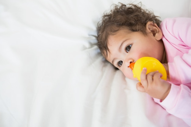 Cute baby holding duck on bed