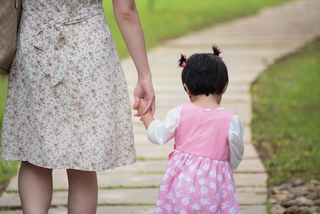 Милый ребенок держит маму за руку и гуляет в саду Premium Фотографии