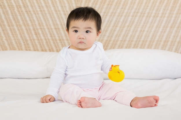 Cute baby holding plastic duck on bed