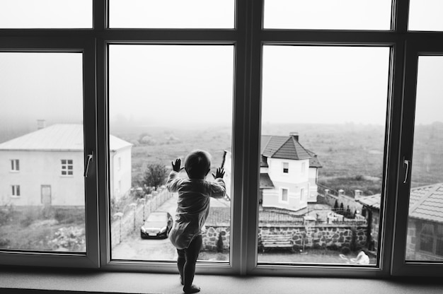 Cute baby at home in white room stands near window
