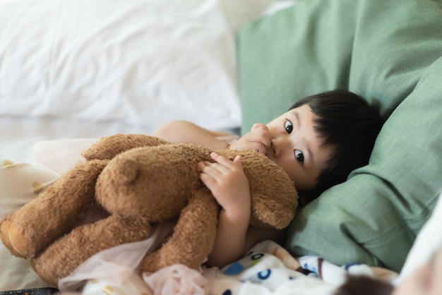 Cute baby hugging teddy bear and sleep on the bed