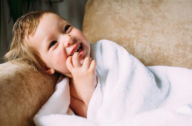 Милый ребенок в большом белом полотенце держит пальцы во рту