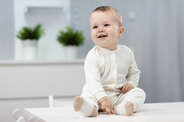 明るい部屋に座っている白いスーツでかわいい赤ちゃん