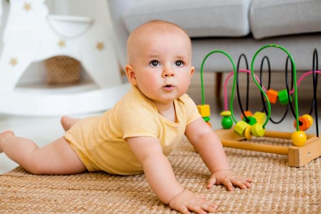 노란색 바디수트를 입은 귀여운 아기가 교육용 장난감을 가지고 노는