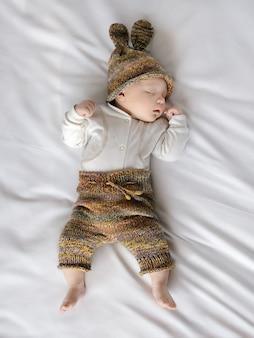 흰색 시트, 아기, 어머니 및 가족의 날에 자고있는 비니와 반바지에 귀여운 아기