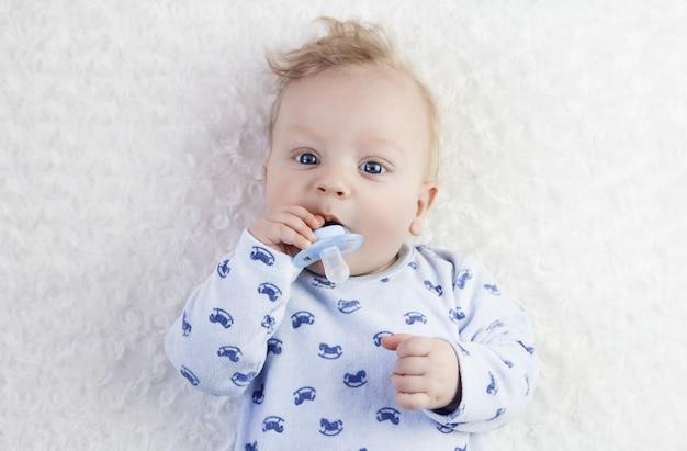 젖꼭지와 파란 잠옷에 귀여운 아기
