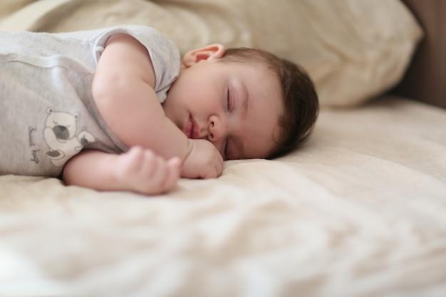 Милый ребенок в мягкой одежде, лежа на кровати и спящий