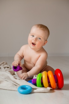 Cute baby is lying in diapers in bed sitting on floor of the house playing with an educational toy