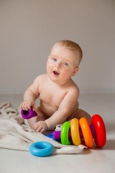 귀여운 아기가 교육용 장난감을 가지고 노는 집 바닥에 앉아 기저귀에 누워 있다