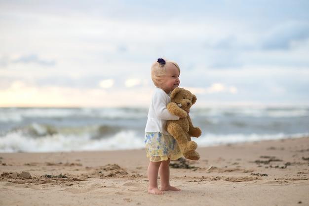 Cute baby little girl with teddy-bear on the beach
