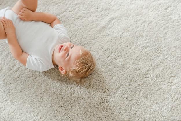 카펫에 누워 귀여운 아기