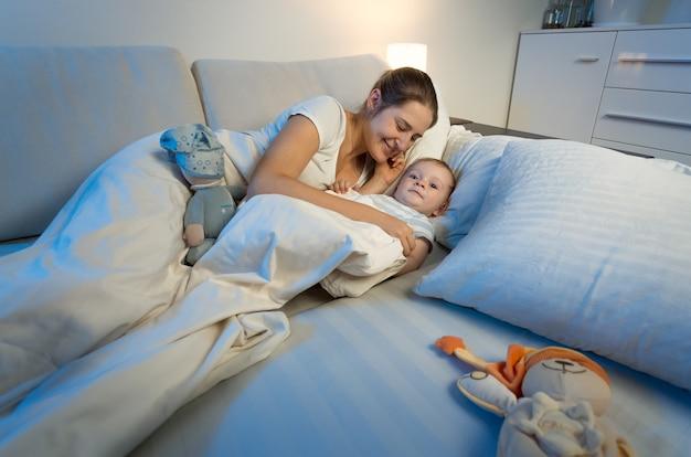 夜のベッドで母親と横になっているかわいい赤ちゃん