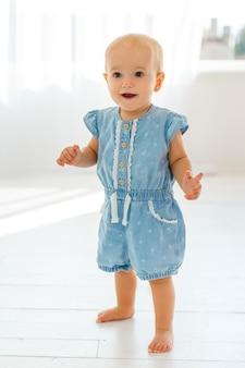 Милый ребенок делает первые шаги. маленькая девочка учится ходить. концепция роста детей и счастливого детства