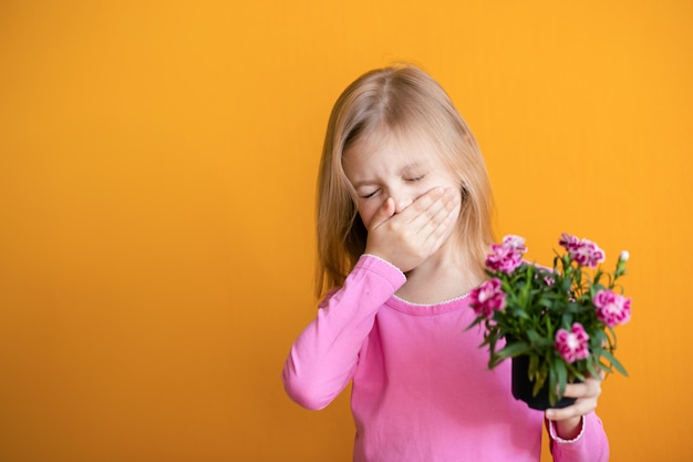 Cute baby on an orange wall, 6-8 years old, a girl in pink clothes sneezes from allergies, holds a pot with a flower of cloves in her hands