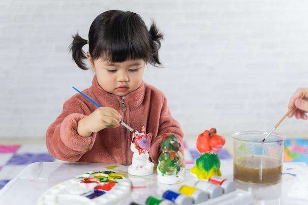 Cute baby painting plaster puppet on the table
