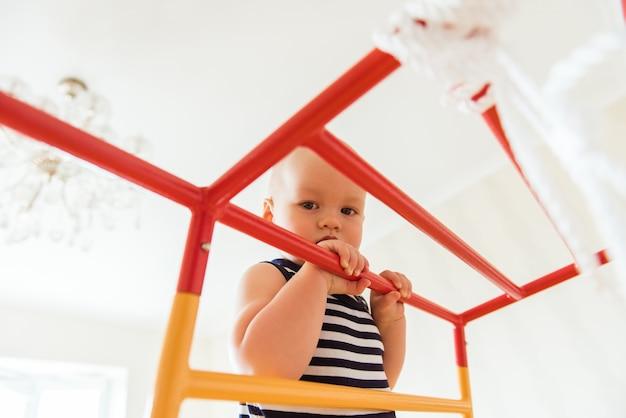 귀여운 아기는 홈 스포츠 단지에서 체조 운동을 수행합니다.