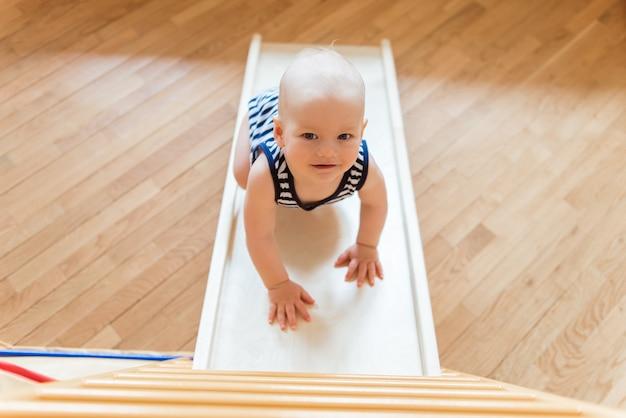 귀여운 아기는 목조 홈 스포츠 단지에서 체조 운동을 수행합니다.