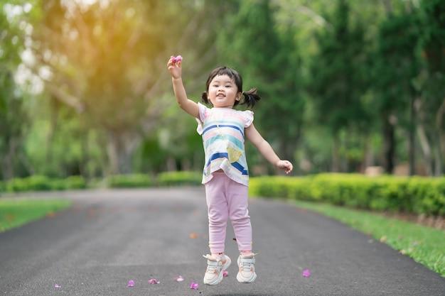 Милый ребенок играет и прыгает в саду, концепция активного отдыха с милым ребенком