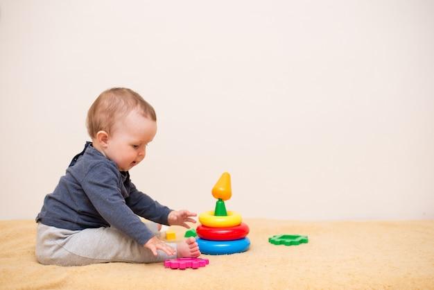 明るい寝室でカラフルなおもちゃピラミッドで遊ぶかわいい赤ちゃん。