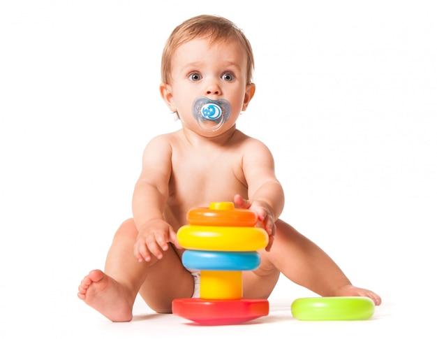 Милый ребенок играет с красочной игрушкой