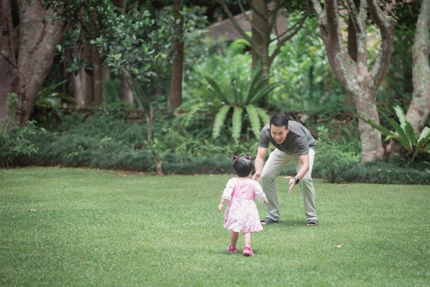 Cute baby playing with father in the garden
