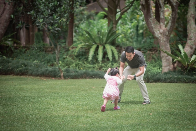 庭で父親と遊ぶかわいい赤ちゃん
