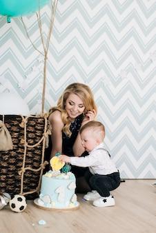 Милый ребенок играет со своей молодой мамой на своем первом детском празднике дня рождения