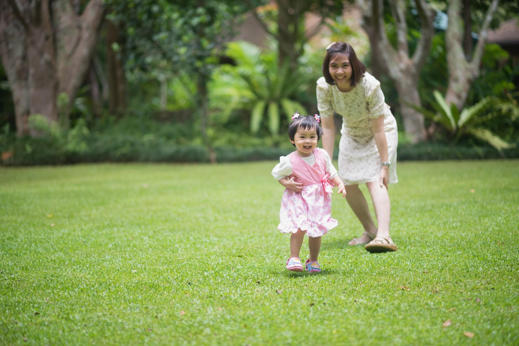 庭で母親と遊ぶかわいい赤ちゃん