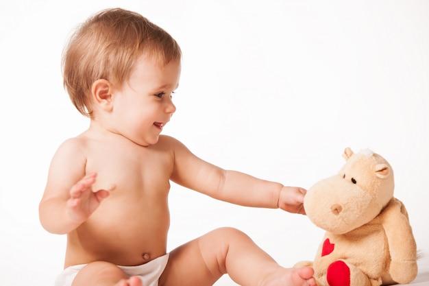 Милый ребенок играет с плюшевой игрушкой