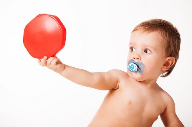 Милый ребенок играет с красной игрушкой